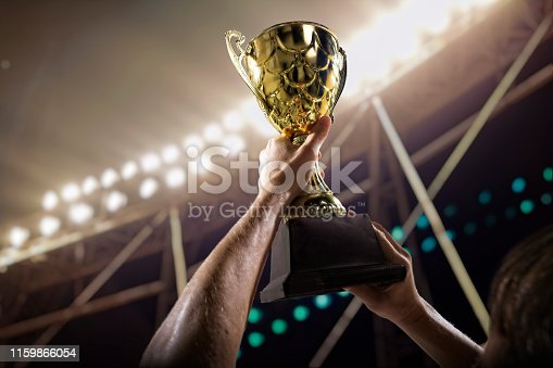 istock Athlete holding trophy cup above head in stadium 1159866054