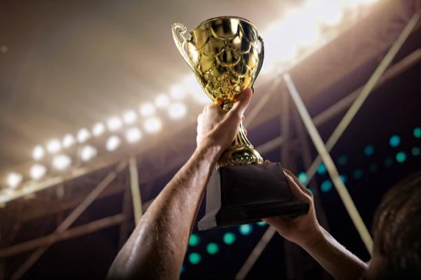 Sportler hält Pokal über Kopf im Stadion – Foto