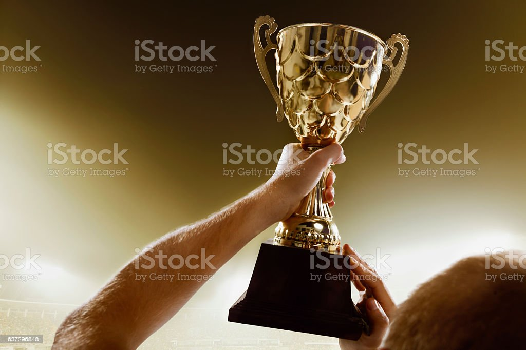 Athlete holding trophy cup above head in stadium stock photo