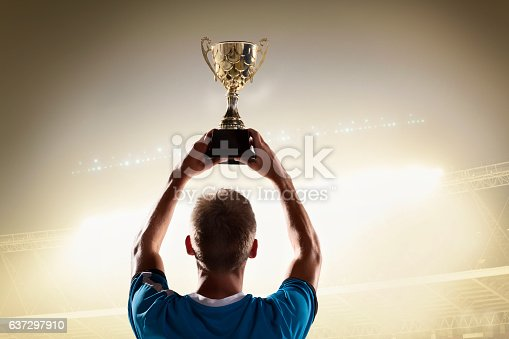 istock Athlete holding trophy cup above head in stadium 637297910