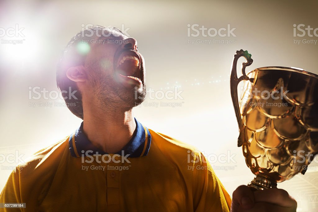 Athlete holding trophy cup in stadium stock photo