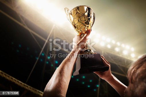 istock Athlete holding trophy cup 517875398