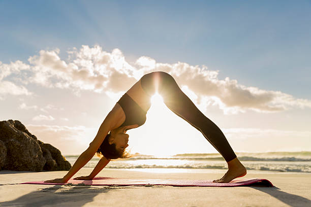 athlete in downward facing dog position on shore - yoga stock photos and pictures