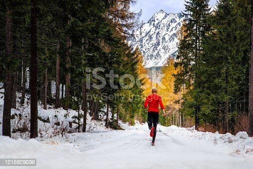 Athlete in red run under winter mountians