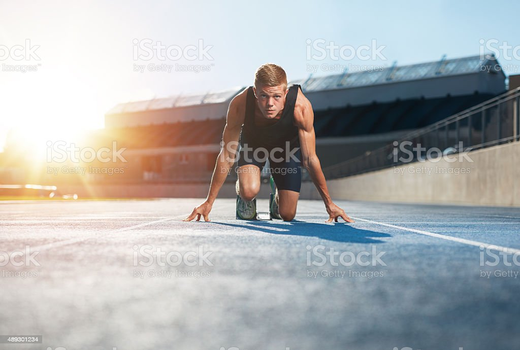 Athlete in starting position ready to start a race stock photo