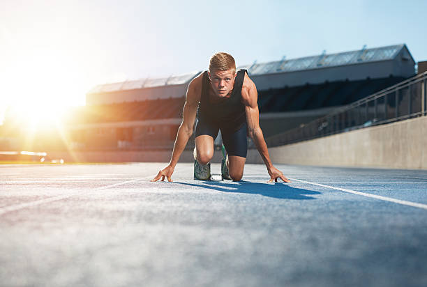 Athlete in starting position ready to start a race Young man athlete in starting position ready to start a race. Male sprinter ready for a run on racetrack looking at camera with sun flare. track starting block stock pictures, royalty-free photos & images