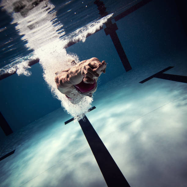 Athlete jumping int the water Underwater shot of a swimmer diving after the jump in the swimming pool. taking the plunge stock pictures, royalty-free photos & images
