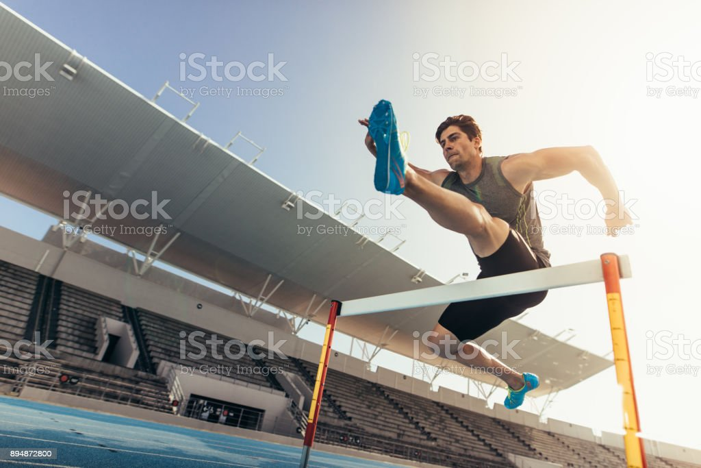 Athlete jumping over an hurdle on running track stock photo