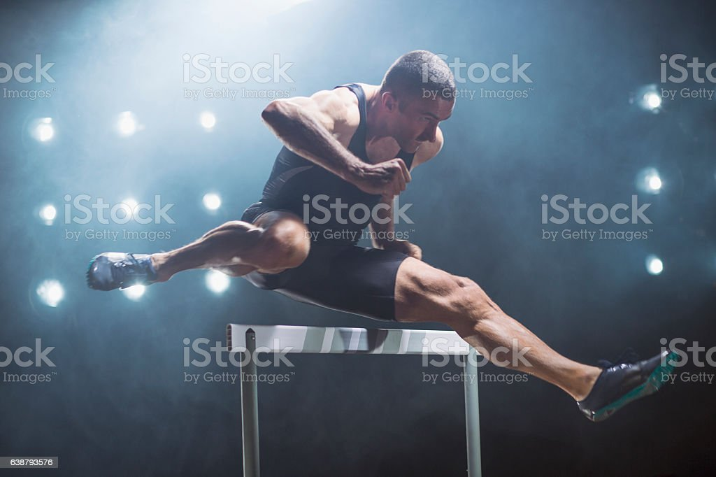 Athlete jumping over hurdle stock photo