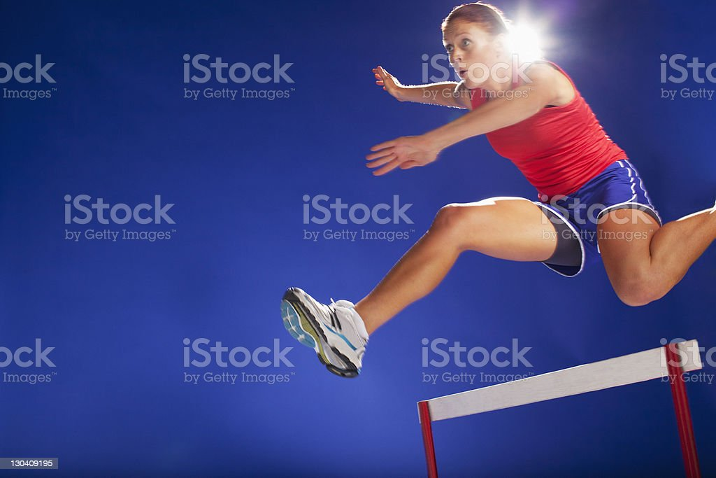 Athlete jumping over hurdles royalty-free stock photo