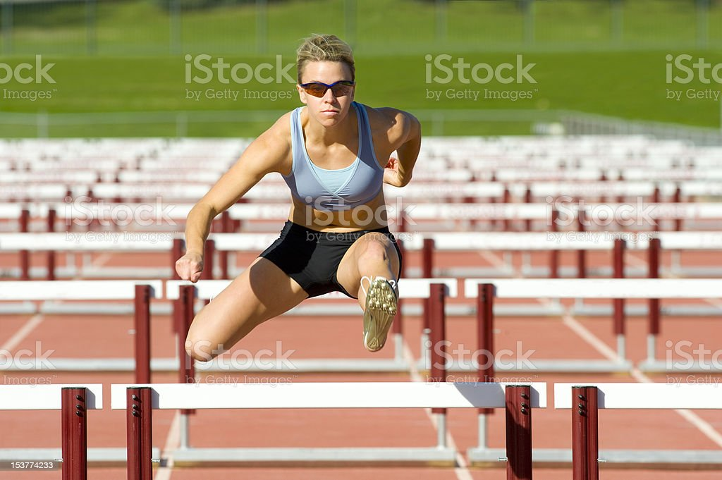 Athlete Jumping over Hurdles stock photo