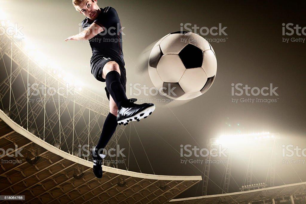 Athlète taper dans un ballon de football au stade - Photo