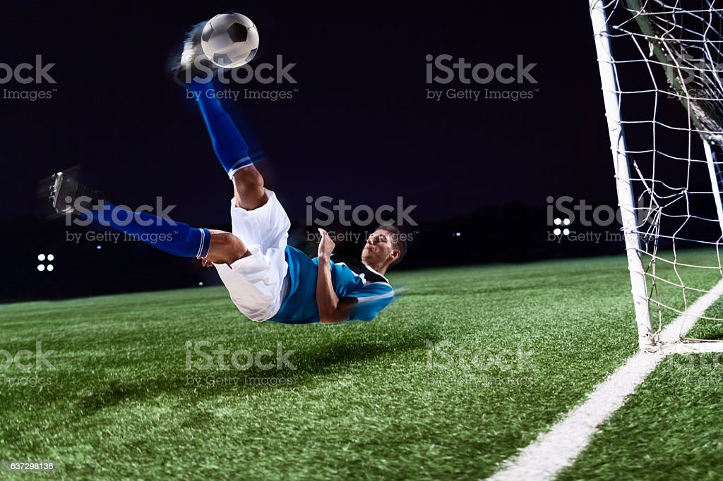 Athlete kicking soccer ball into a goal stock photo