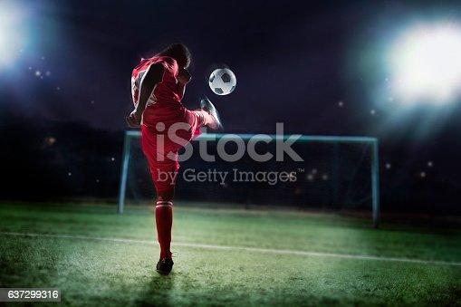 istock Athlete kicking soccer ball into a goal 637299316