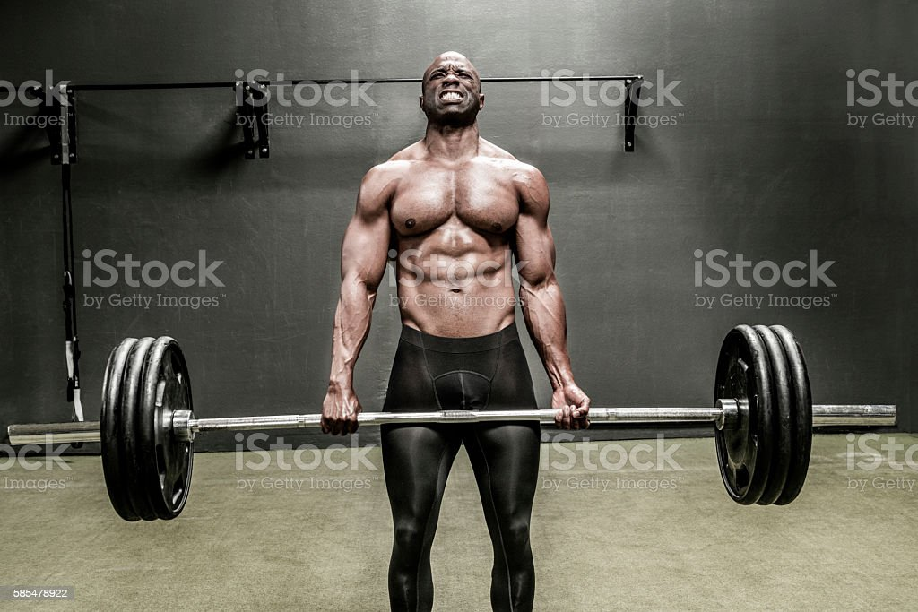 Athlete lifting heavy weight bar stock photo