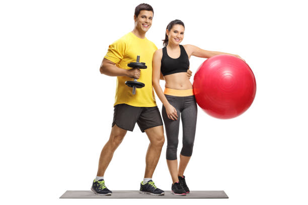 Athlete male and female with a dumbbell and pilates ball stock photo