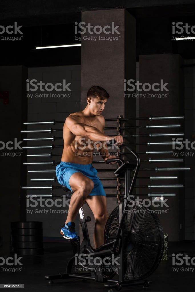 Atleet man fietsen in de sportschool royalty free stockfoto