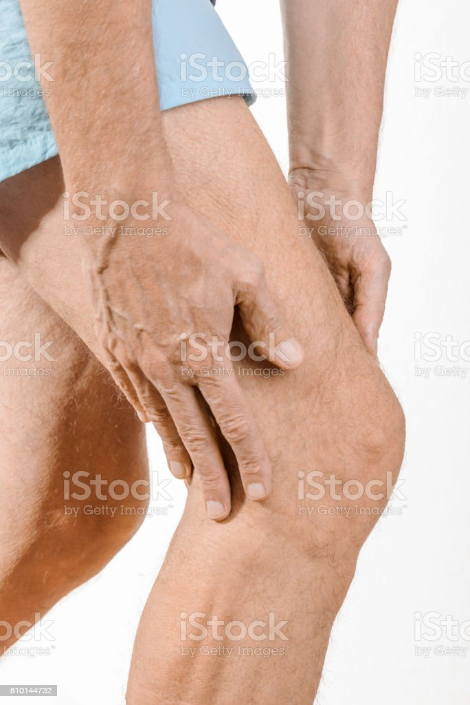 Athlete man feeling pain to the knee and to the quadriceps stock photo