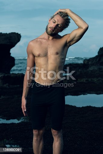 Athlete man practicing yoga on a rock on a beach with ocean background