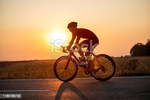 Young professional athlete riding bicycle for exercise on the road through the countryside. He is well equipped, with protective helmet, sunglasses, black and red jersey. Photo taken when cyclist is in motion. Sunset in background makes him silhouette.
