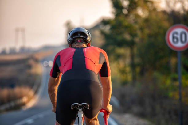 Athlete man riding bicycle on the road stock photo