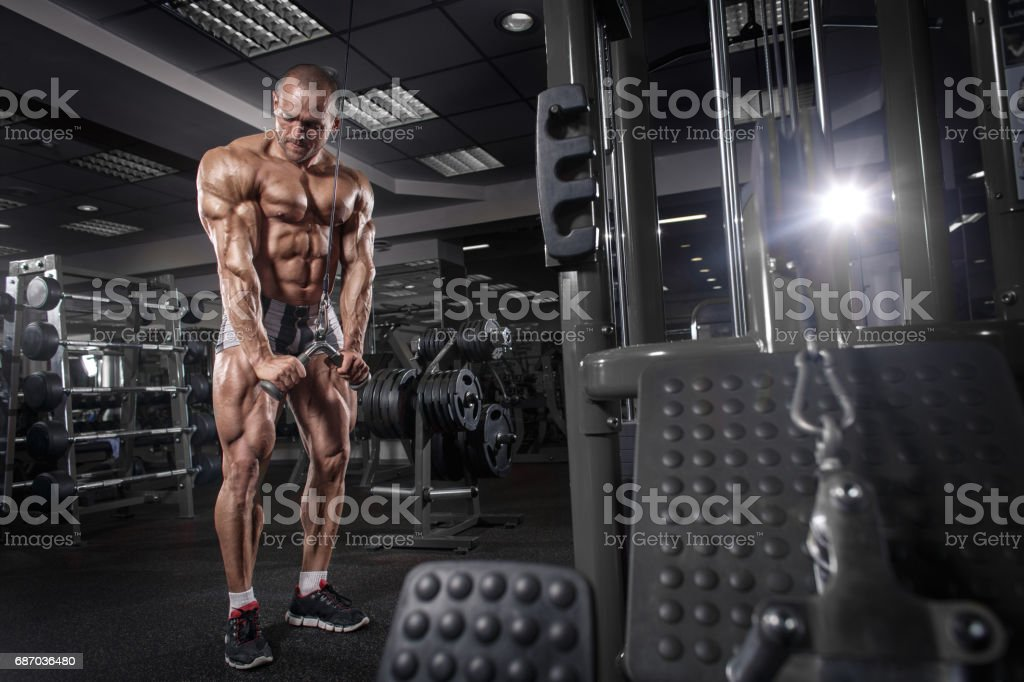 Athlete Muscular Bodybuilder Training On Simulator In The