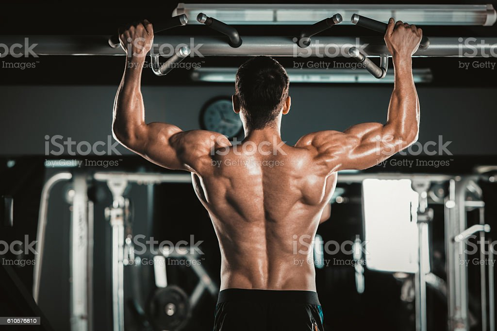 Athlete muscular fitness male model pulling up on horizontal bar stock photo