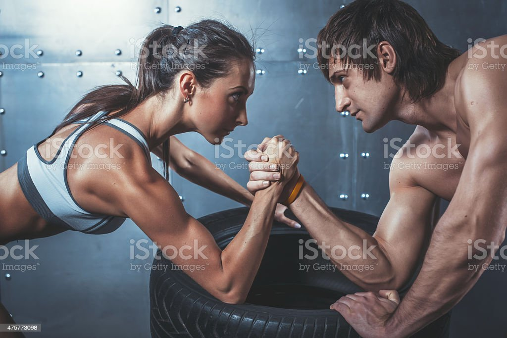 Athlete muscular sportsmen man and woman with hands clasped arm stock photo