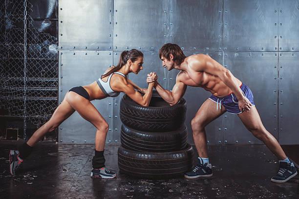 sportler muskeln sportler mann und frau mit hände befinden sich verschränkt arm - armdrücken stock-fotos und bilder