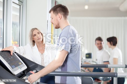 istock athlete on a treadmill with physiotherapist doctor 862679296