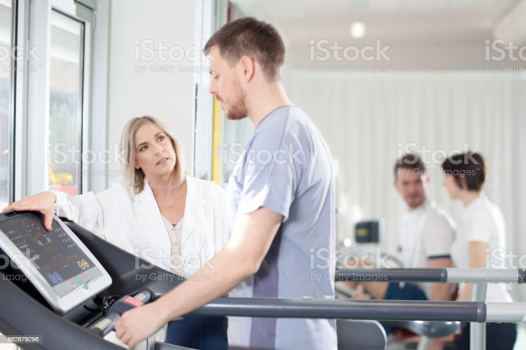 athlete on a treadmill with physiotherapist doctor stock photo