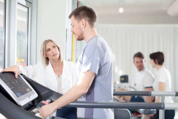 athlete on a treadmill with physiotherapist doctor - cardiologist stock pictures, royalty-free photos & images