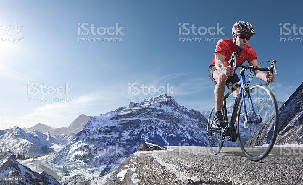 athlete on racing bike cycling through alpine mountains