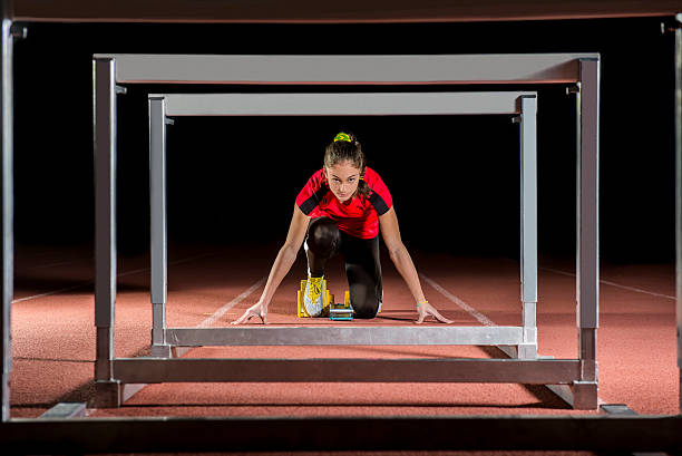 Athlete on the starting blocks with hurdles stock photo