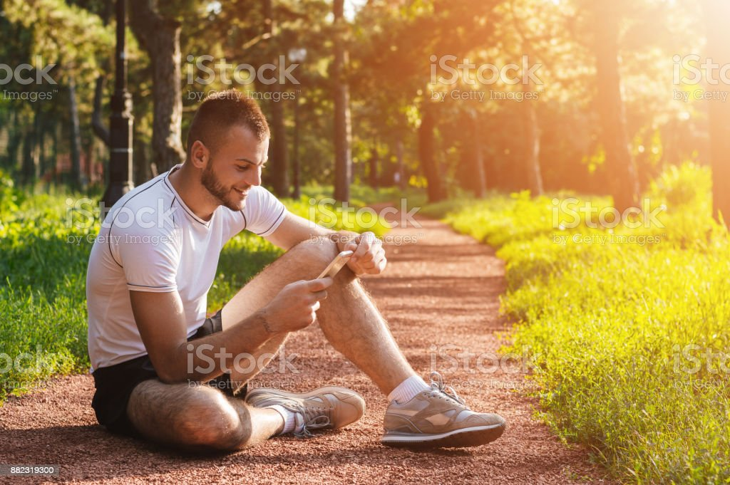 Athlete or sports trainer checking his mobile phone in the park