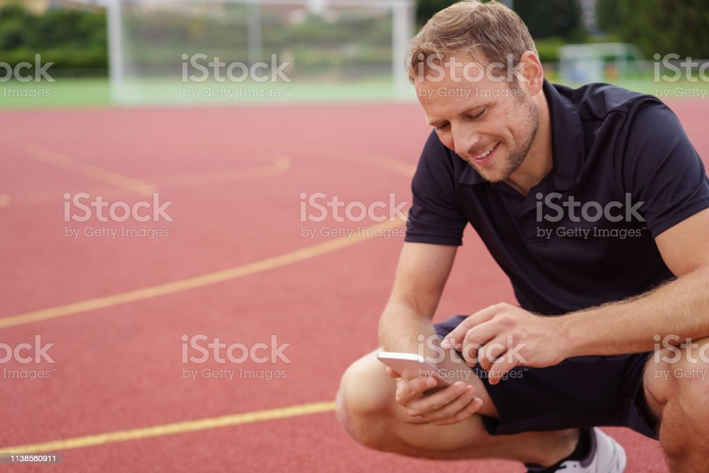 Athlete or sports trainer checking his mobile phone for messages as...