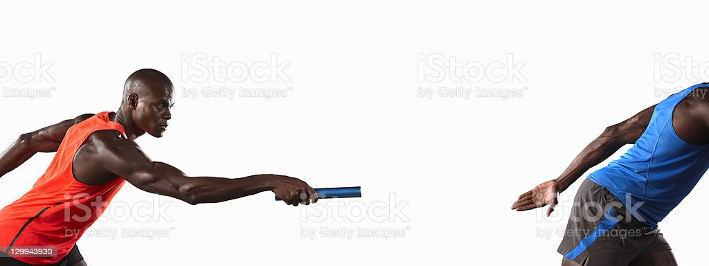 Athlete passing relay baton stock photo