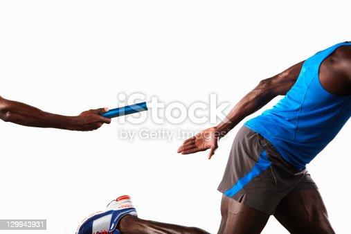istock Athlete passing relay baton 129943931
