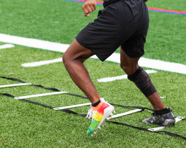 Athlete performing ladder drills on sports field A high school boy is running ladder drills with colorful cleats on a turf field during summer camp practices. high school sports stock pictures, royalty-free photos & images