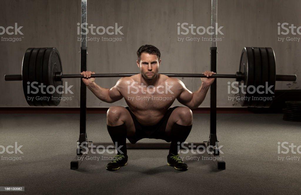 Atleta realiza squat con barra para pesas - Foto de stock de Agacharse libre de derechos