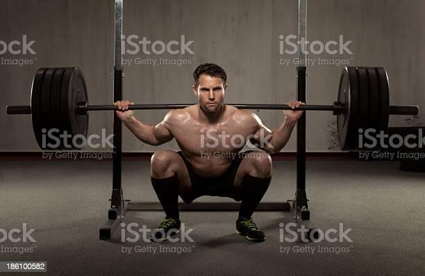 Atleta Realiza Squat Con Barra Para Pesas Foto de stock y más banco de imágenes de Agacharse