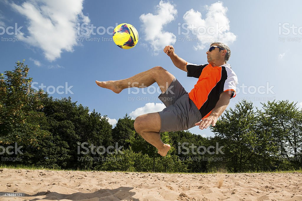 athlete playing beach soccer stock photo