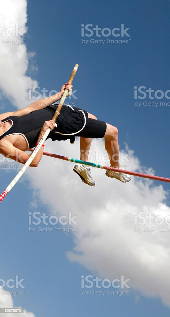 Athlete pole vaulting on a sunny day against sky background stock photo