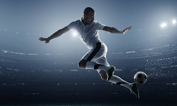 Athlete posed kicking a soccer ball in a stadium stock photo