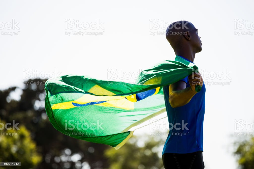 Athlete posing with brazilian flag after victory stock photo