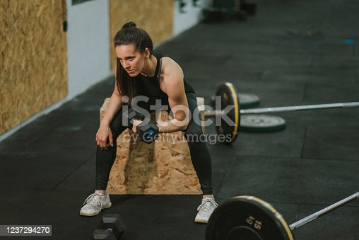 Attractive young woman is doing her gym training with barbells