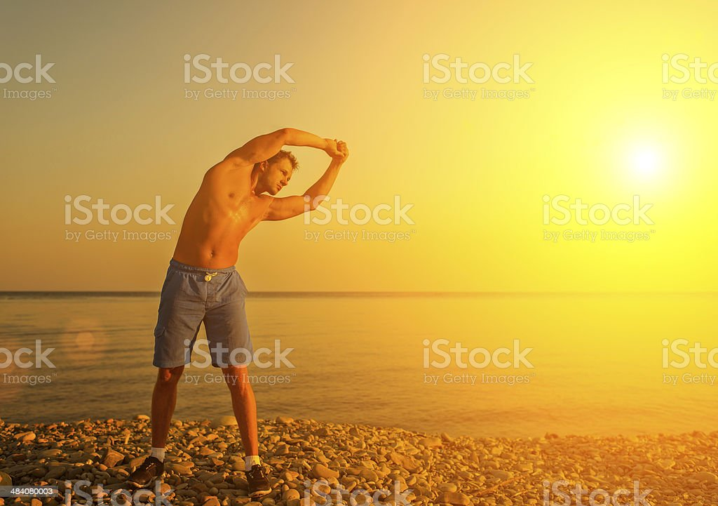 athlete practicing, playing sports and yoga on beach at sunset royalty-free stock photo