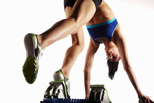 atleta in blocchi di partenza mettendo il piede - corsa su pista femminile foto e immagini stock