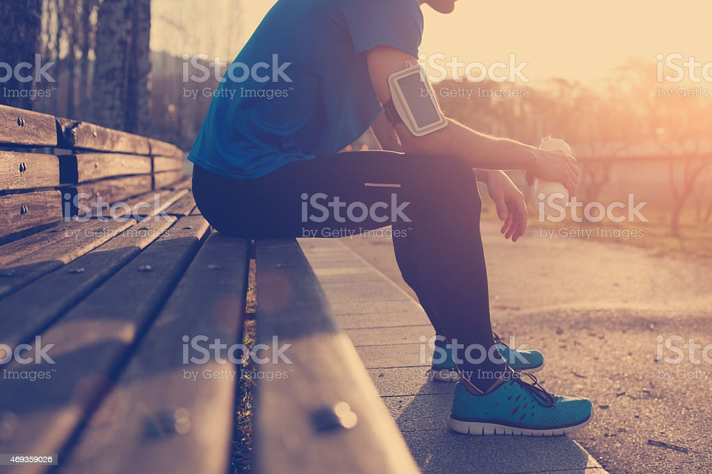 Athlete resting on bench at sunset stock photo