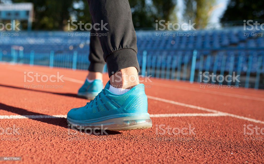 Athlete runner feet running on road closeup on shoe. Man fitness jog workout wellness concept. Man runner legs and shoes in action on road royalty-free stock photo